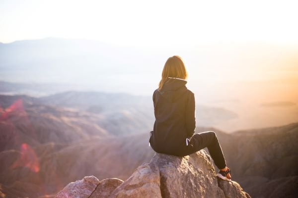 Woman sitting on rock peak facing away